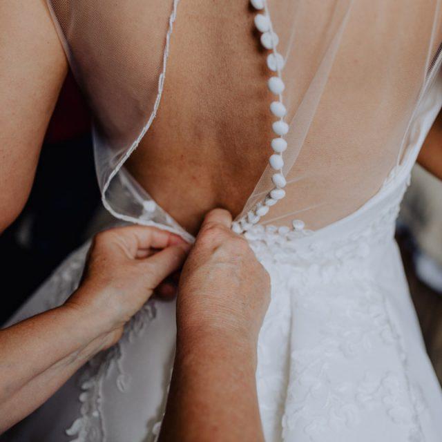 Braut ihr Hochzeitskleid anziehen