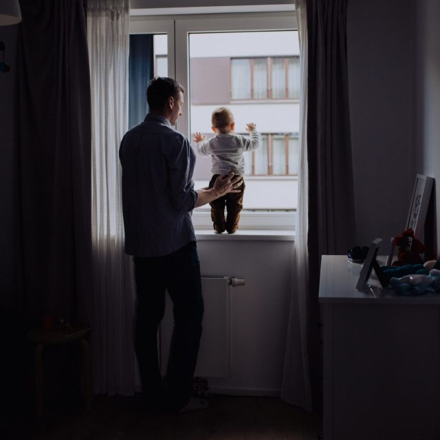 boy standing at the windown with father